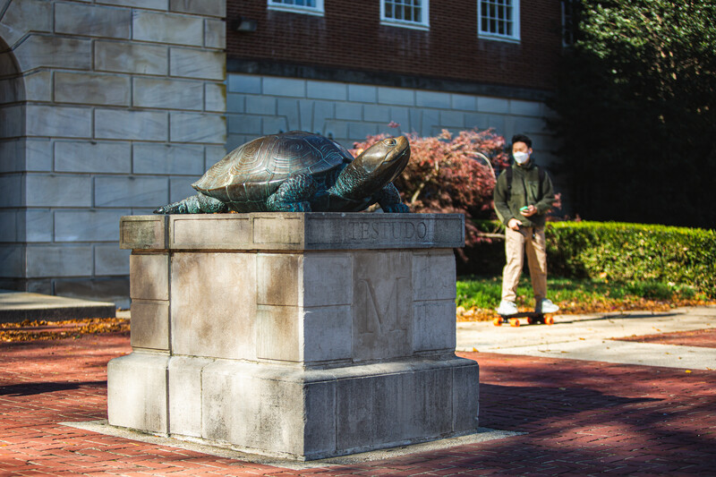 View of Testudo statue in front of McKeldin Library with fall foliage and a student walking by wearing a mask.